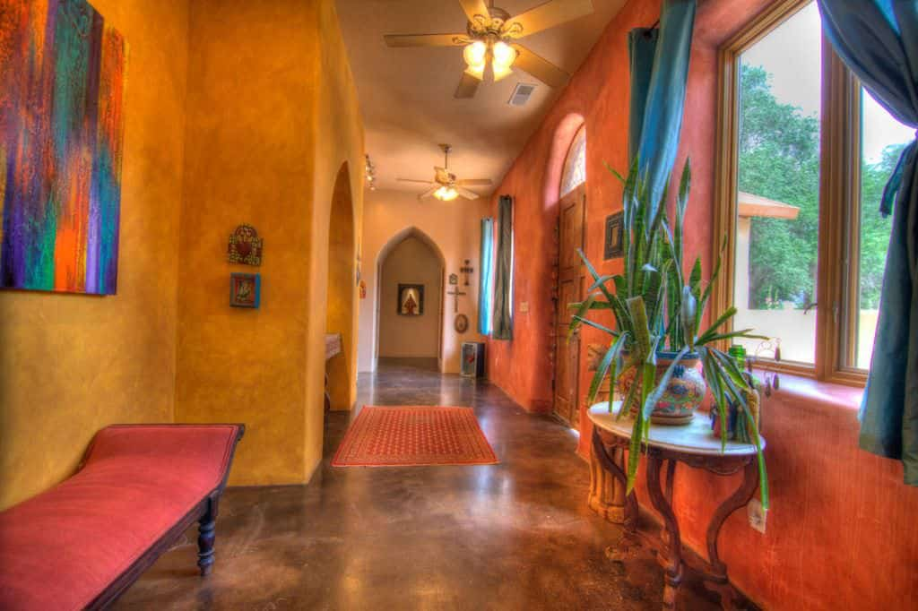 This colorful foyer features a smooth walls and flooring. The wall decors and curtains add style to the home. The red seat on the side looks perfect as well.