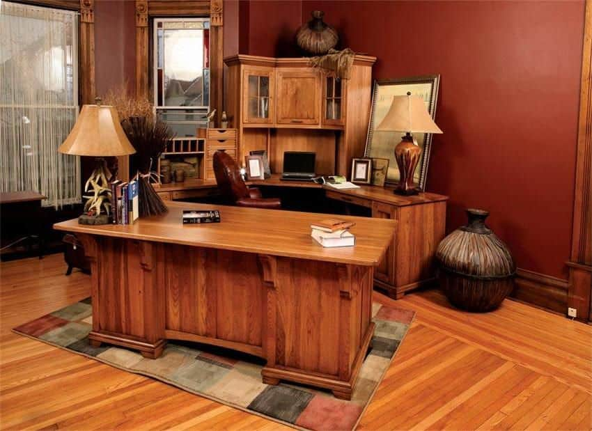 Craftsman home office with curved and wooden desks that sit on a checkered rug over hardwood flooring. It includes table lamps and antique jars.
