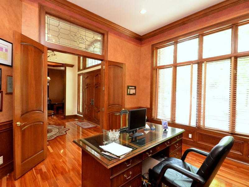 Warm home office boasts a rich hardwood flooring and glass windows that bring natural light in. It includes a wooden desk paired with a black leather chair.