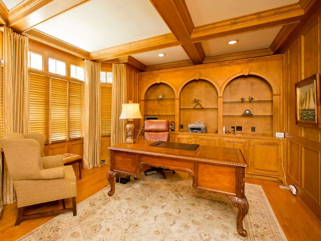 Traditional home office with coffered ceiling, built-in shelving and hardwood flooring with a rug.
