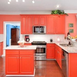 Eclectic orange kitchen with white backsplash.
