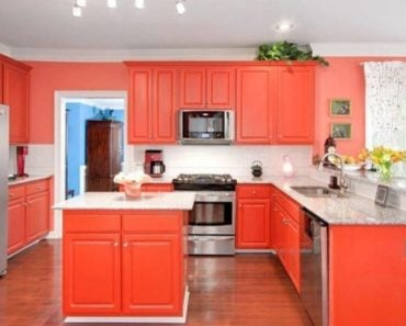 Eclectic orange kitchen with white backsplash.