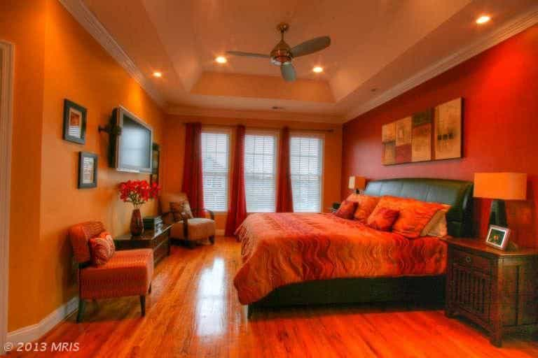 Mid-sized contemporary master bedroom. with tray ceiling, orange walls and hardwood flooring.