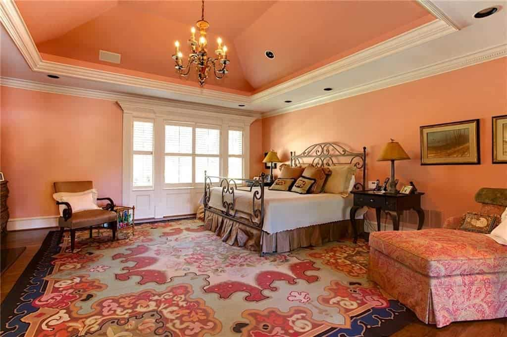 A vintage chandelier that hung over the ornate metal bed illuminates this coral pink bedroom featuring a floral chaise lounge and brown armchair that sits on the lovely rug.