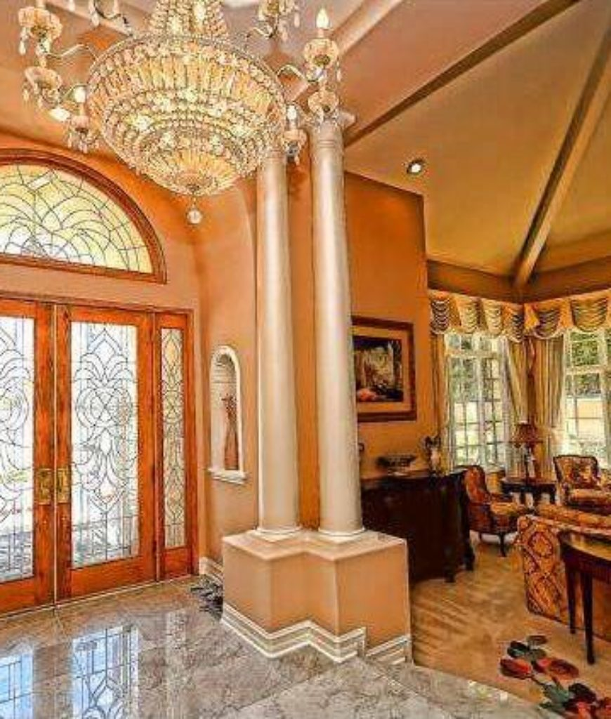 Traditional foyer with crystal chandelier, French doors and marble tile floors.
