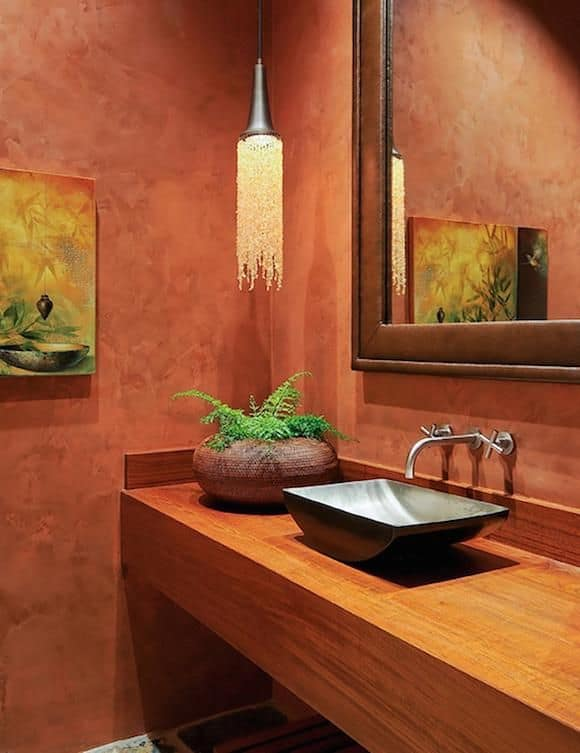 Warm bathroom lighted by a fancy crystal pendant that hung over a built-in vanity topped with a black vessel sink and plant decor.