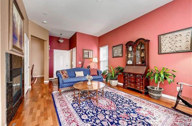 Large Traditional Living Room With Pink Walls, A Stone Fireplace And  Hardwood Flooring With A Large Rug.Source: Zillow Digs