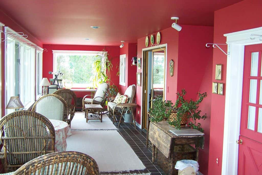 Traditional pink sunroom with indoor plants, wicker chairs and tile flooring with rugs.