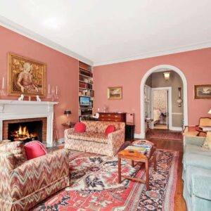 Large Traditional living room with pink walls, arched doorway and a brick fireplace.