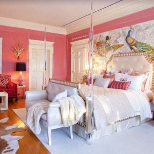 Elegant pink primary bedroom with chandelier table lamps, accent chairs and a large artwork behind the posh four poster bed.