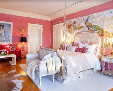Elegant pink master bedroom with chandelier table lamps, accent chairs and a large artwork behind the posh four poster bed.