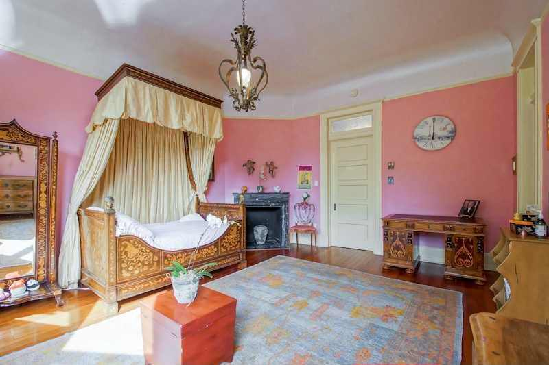 Large Traditional pink master bedroom with cove ceiling, an elegant valance over the single size bed and an ornate fireplace.