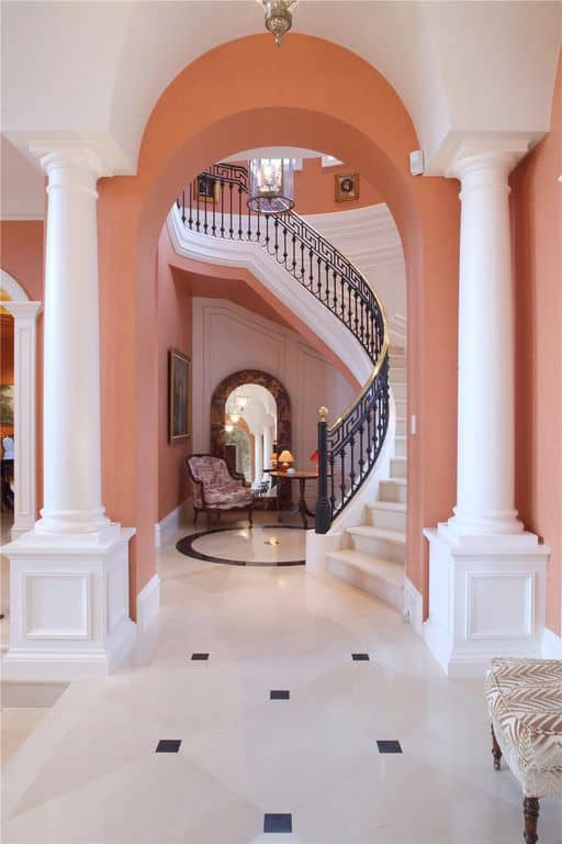 This foyer features a stylish flooring and peach-colored walls. The staircase looks glamorous while the chair underneath looks classy.