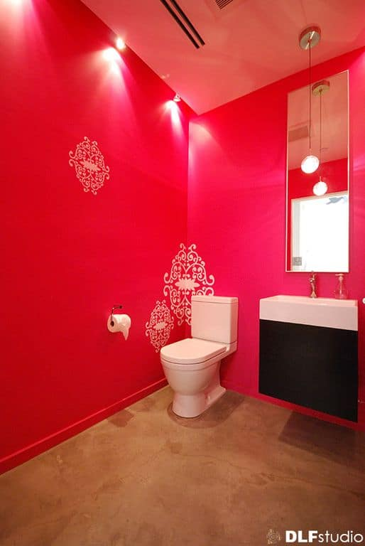 Pink bathroom with a toilet and a sleek vanity sink paired with a frameless mirror and illuminated by a round pendant along with track ceiling lights.