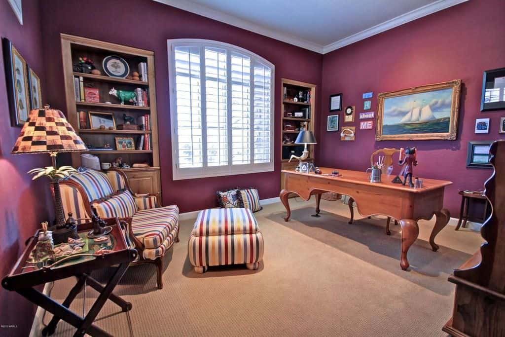 Country style home office with purple walls, built-in shelving and carpet flooring.