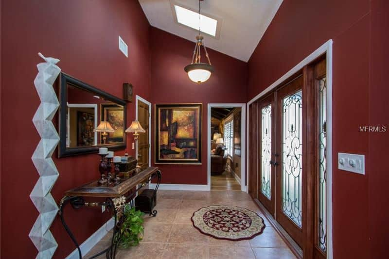 This foyer boasts stylish red walls along with white details. The tiles flooring is topped by a rug. The ceiling offers a skylight and an elegant pendant light.