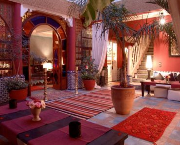 Large Eclectic foyer with columns, indoor plants and runner rugs over slate flooring.