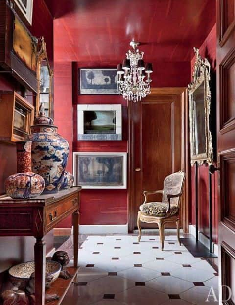 Red foyer featuring a chandelier lighting and stylish set of decors. The chair on the corner looks enchanting.