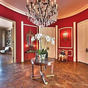 Large Traditional foyer with crystal chandelier, crown molding and hardwood floors.