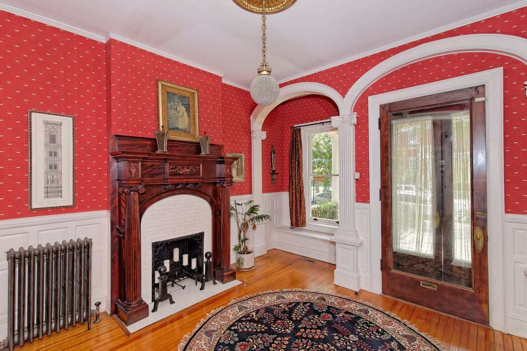 Traditional foyer with red interior wallpaper, a fireplace and a window seat.