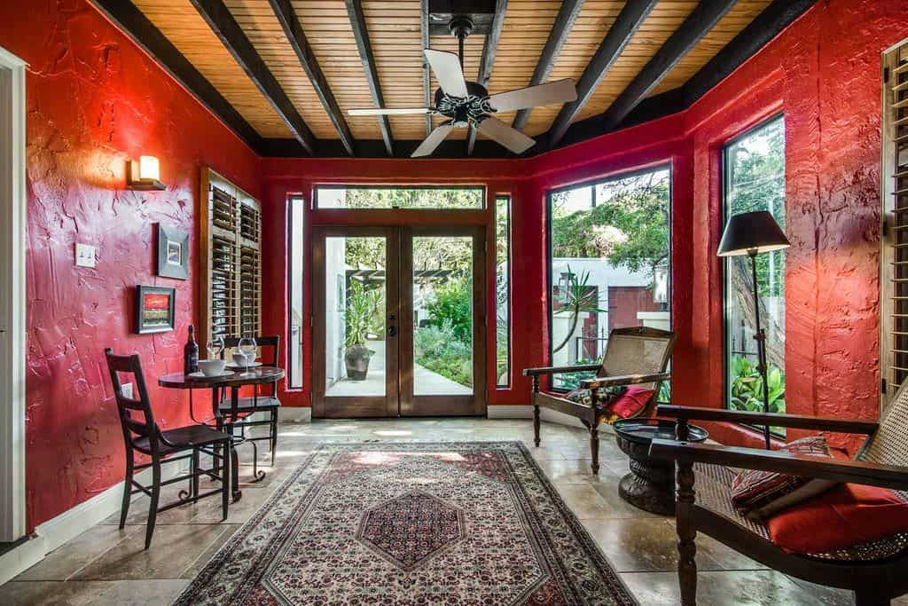This foyer is surrounded by red walls. The seats look comfortable. The glass door and windows look beautiful.
