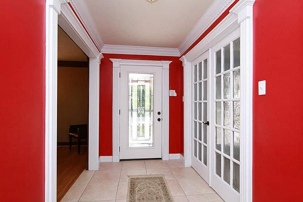 Traditional foyer with red walls, French doors and tile flooring.