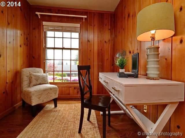 An all wood home office features wood plank walls fitted with a picture window. It has a white comfy chair along with a black wooden chair that sits at a white office desk topped with a table lamp.