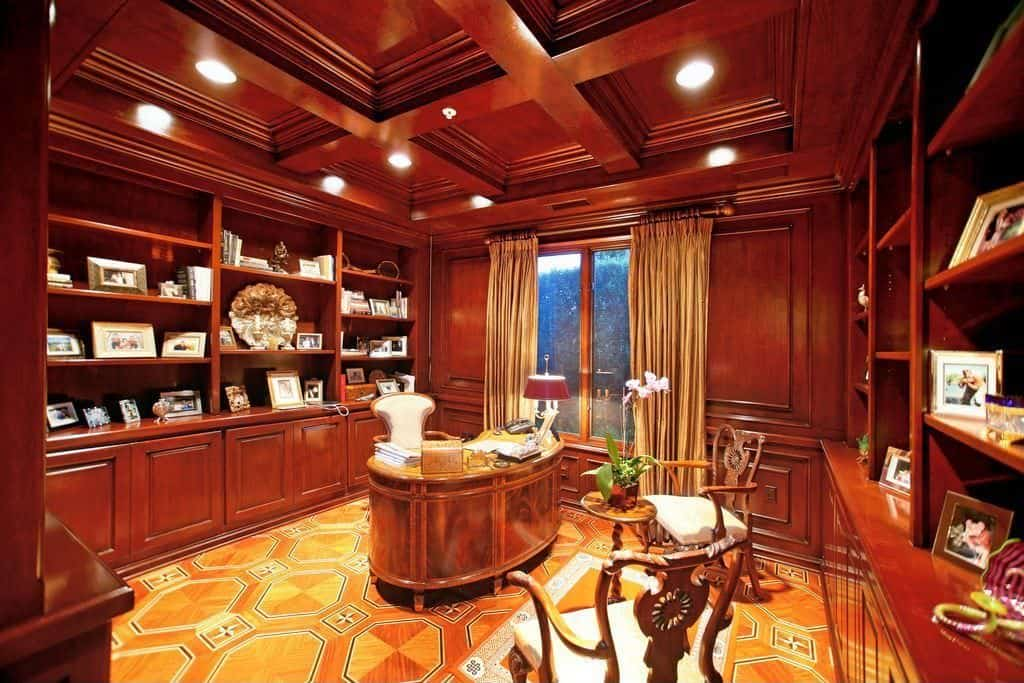 Large Traditional home office with coffered ceiling, built-in shelving and carpet flooring.