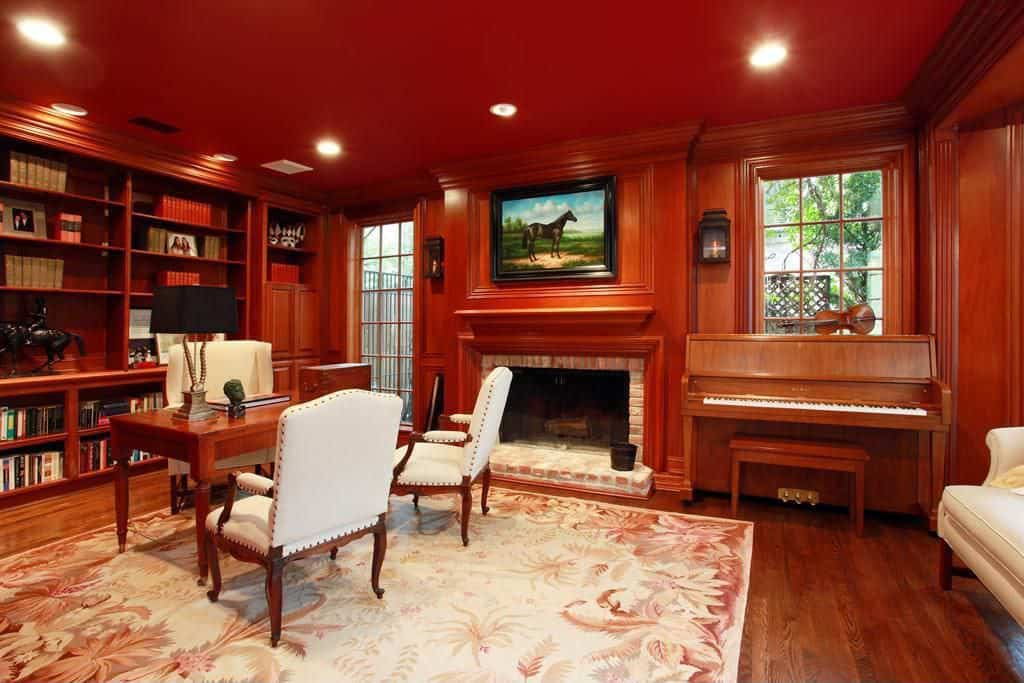 Large Traditional Home Office With Red Walls Built In Shelving And A Fireplace Side