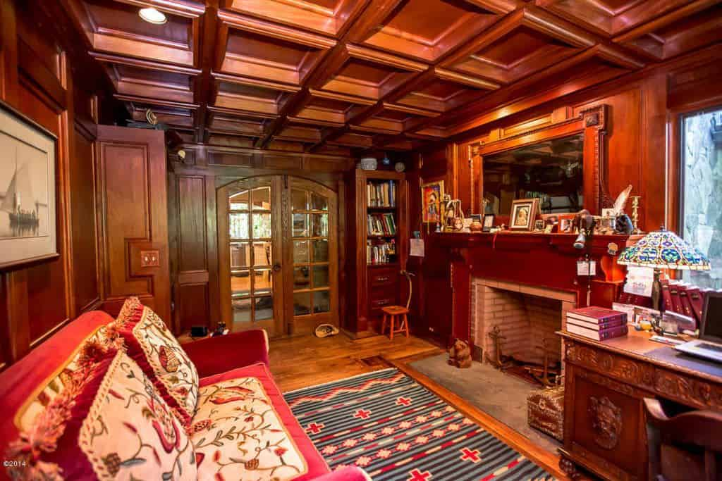 Traditional home office with coffered ceiling, French doors, a fireplace and a sofa.