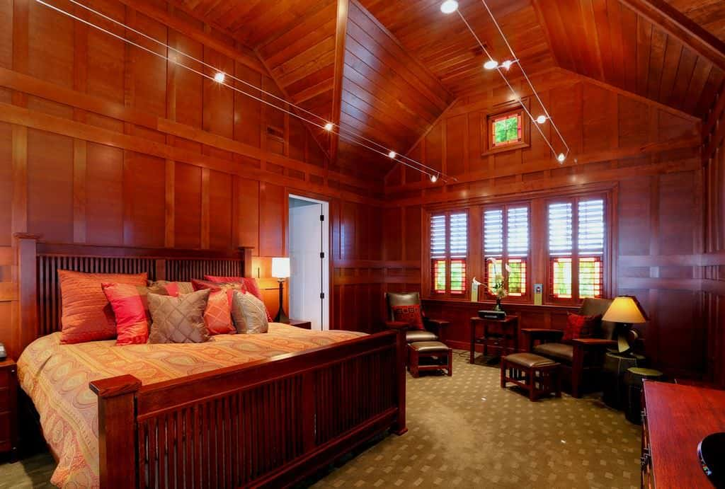 This primary bedroom offers a cozy seating area and a wooden bed that blends in with the wood paneled walls. It has green carpet flooring and a high cathedral ceiling clad in wood planks.