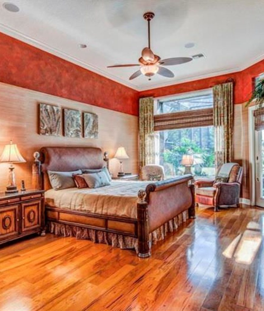 Traditional Master Bedroom With Ceiling Fan Light Red Interior Wallpaper And A Cozy Seating Area