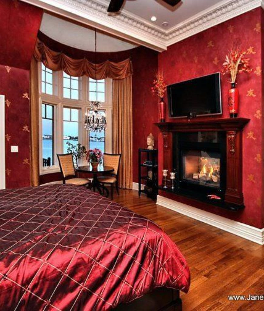 Traditional Master Bedroom With Red Interior Wallpaper A Fireplace And Chandelier Over The Seating