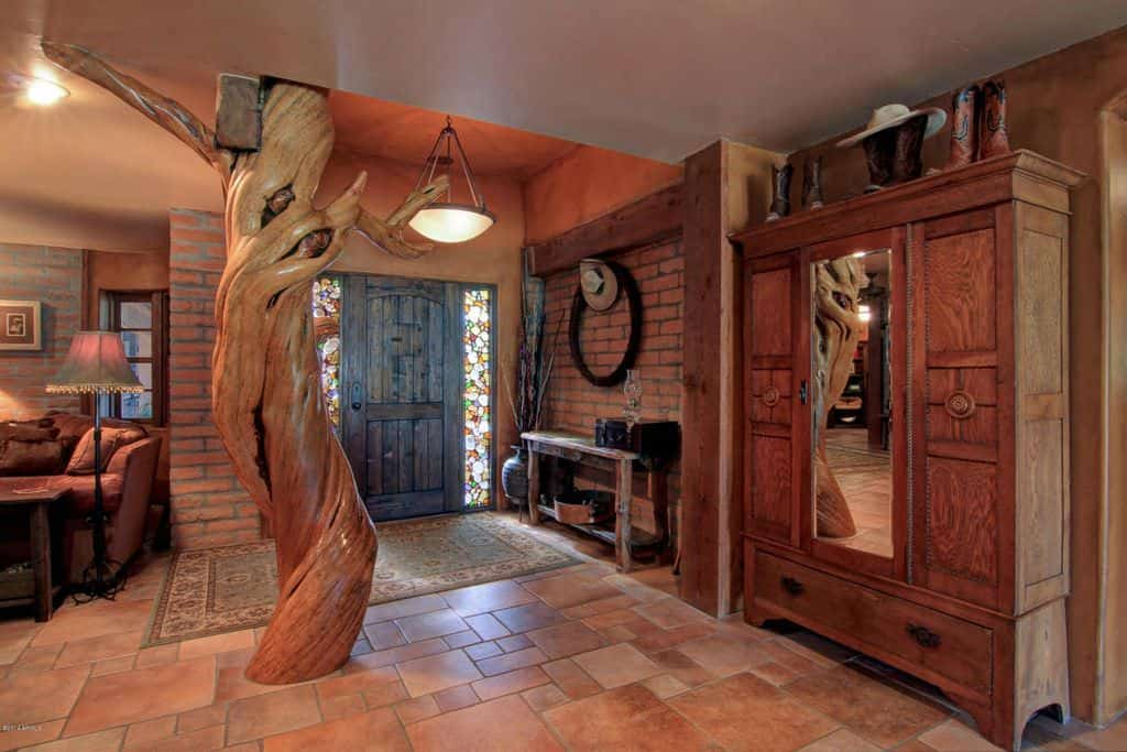 Rustic foyer showcases red brick walls and a wooden front door lined with stained glass. It is highlighted by a decorative trunk column fixed on the terracotta tiled flooring.