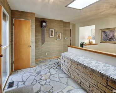 Rustic foyer with a skylight, interior gray wallpaper, stone brick half wall and flagstone flooring.