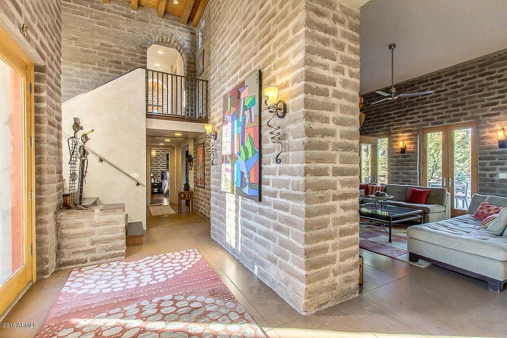 This gorgeous foyer boasts brick walls and tiles flooring. Wall lighting adds elegance to the home.
