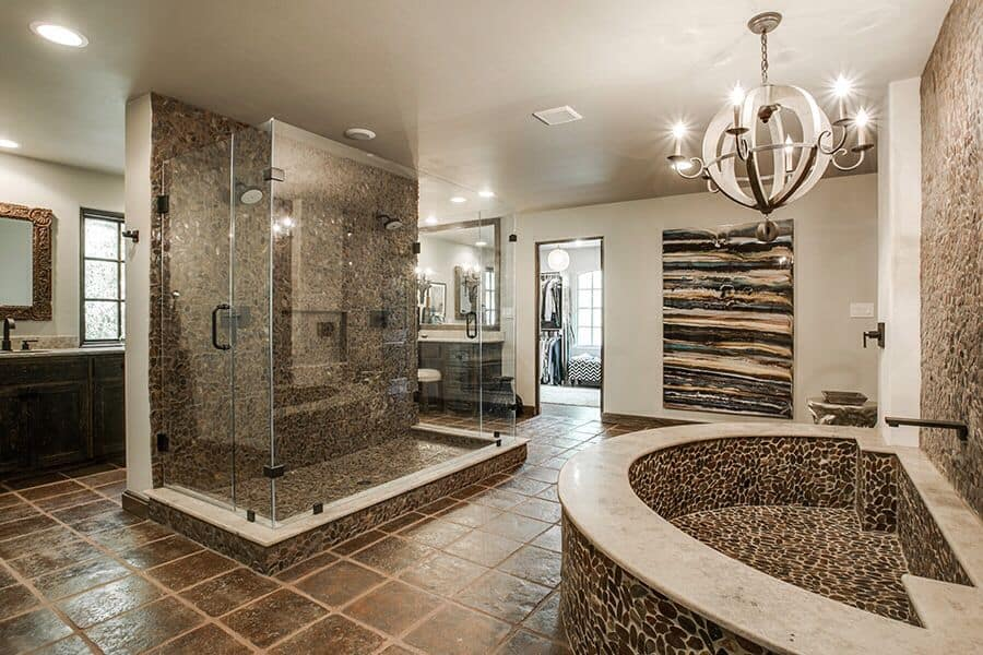 Rustic primary bathroom with a chandelier, stone accent walls and tile flooring.