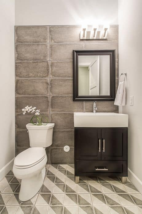 White and brown powder room with accent all and diagonally striped floors.
