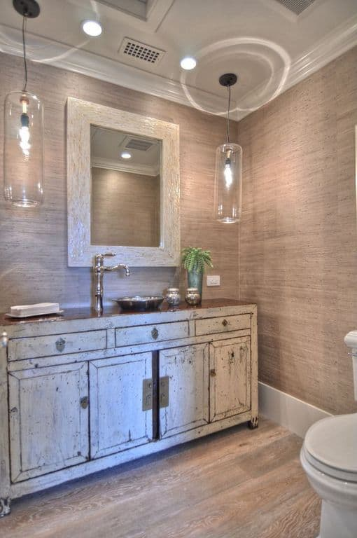 This bathroom boasts a distressed vessel sink vanity lighted by cylindrical glass pendants that hung from the white ceiling with crown molding.