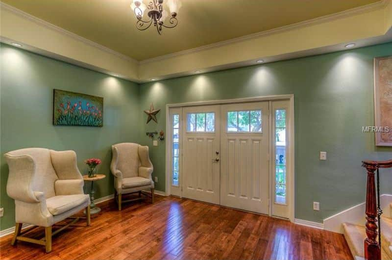 This home features a green walls-themed foyer featuring hardwood flooring and recessed lighting set on the tray ceiling.