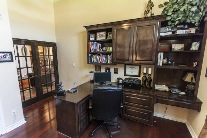 Traditional home office with a black office chair that sits at a dark wood built-in desk with shelving complementing the french door that leads to the living room.