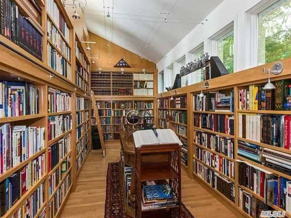 Traditional library with shed ceiling and hardwood flooring.