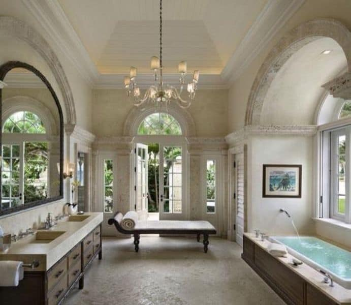 Shabby-chic primary bathroom with beam ceiling, undermount sinks and a drop-in bathtub.
