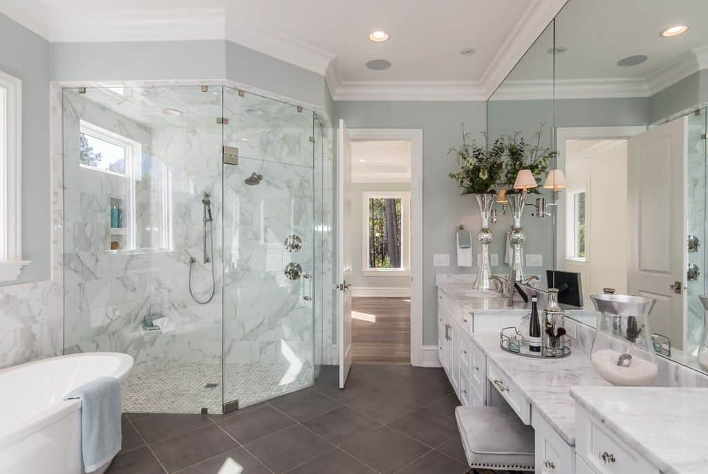 A giant walk in shower sits in one corner of this master bath in a cut square corner shape, with huge glass panels creating the enclosure. White and gray accented tile with a marbled pattern make this look like you are in a snowy wonderland. White cabinets line the opposite wall with marble countertops and ceiling to vanity mirroring fill every inch of the wall space.