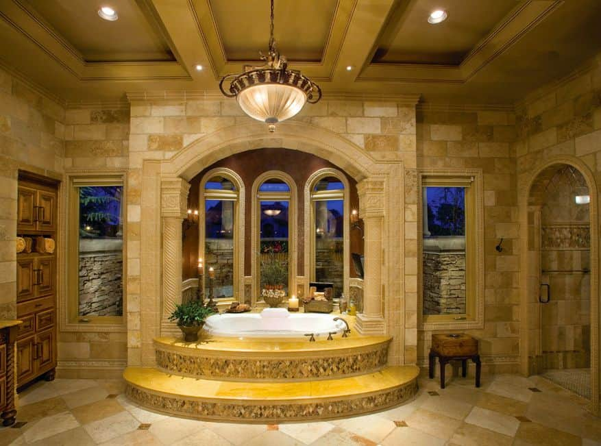 Mediterranean primary bathroom with tray ceiling, pendant lighting and a drop-in tub.