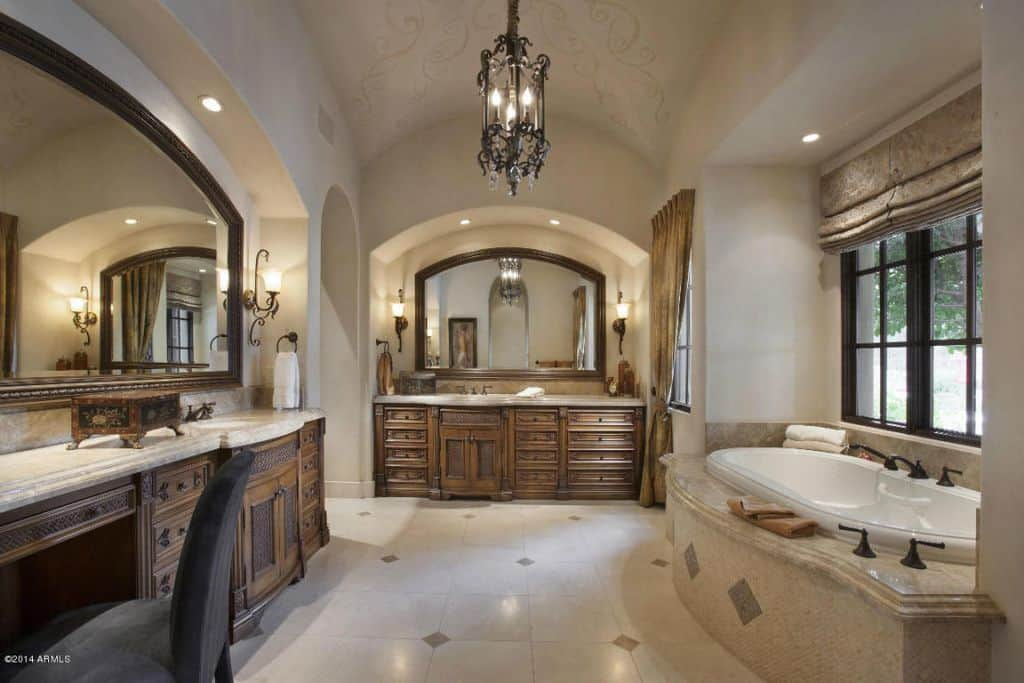 Traditional master bathroom with barrel vault ceiling, arched doorway, undermount sink and a drop-in tub.