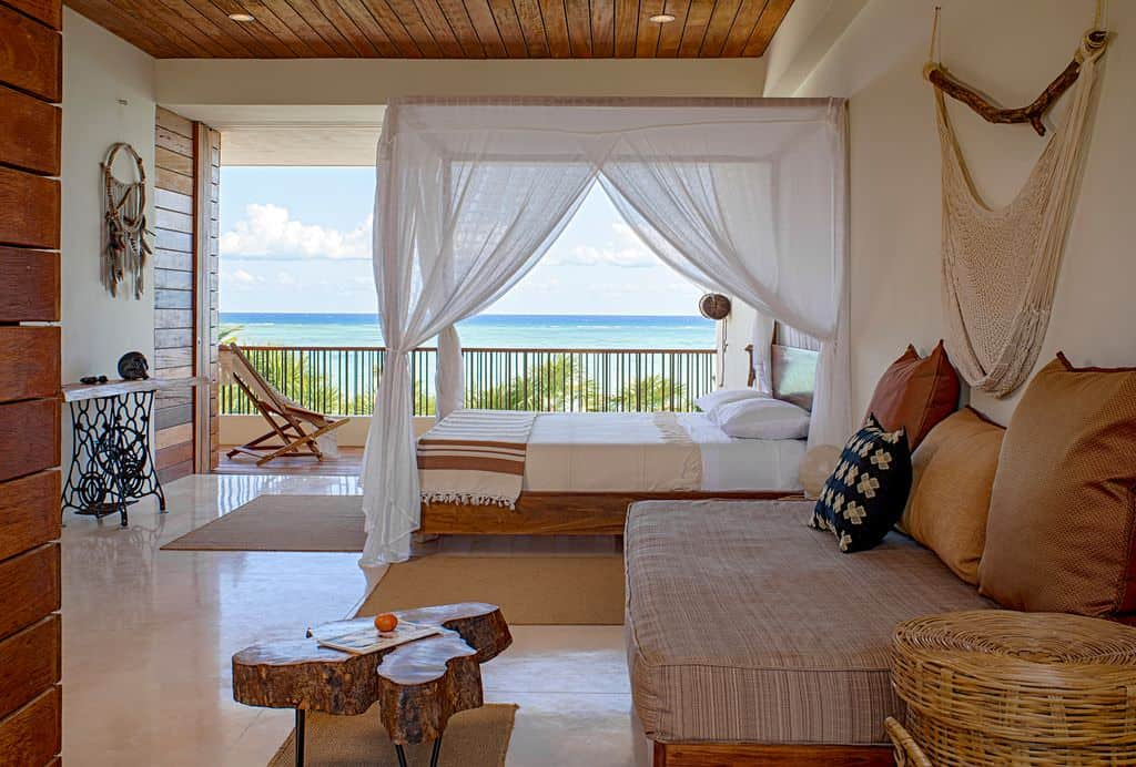Mid-sized island style primary bedroom with a balcony overlooking a magnificent beach view. It features a canopy bed and boho decors that create a relaxing vibe in the room.