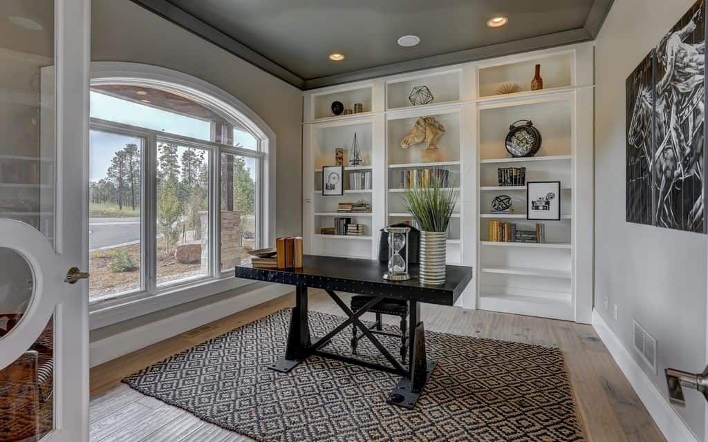 White home office with black office table set on the stylish rug covering the hardwood flooring. The room features a handsome black ceiling lighted by recessed lights.