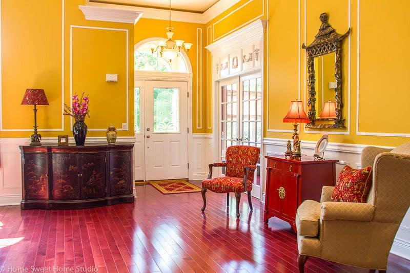 This foyer features yellow walls and red flooring. The chairs both matches the walls and the flooring.