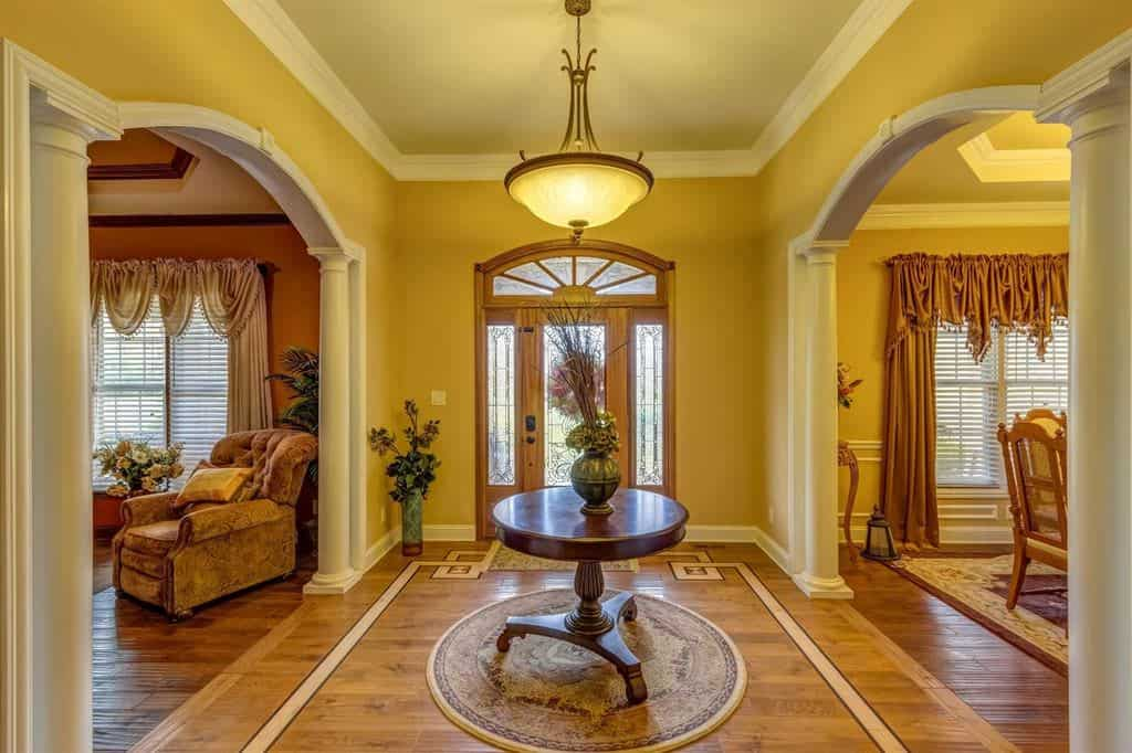 Warm foyer lighted by a pendant that hung over a wooden center table. It sits on a round rug in between open archways lined with columns.